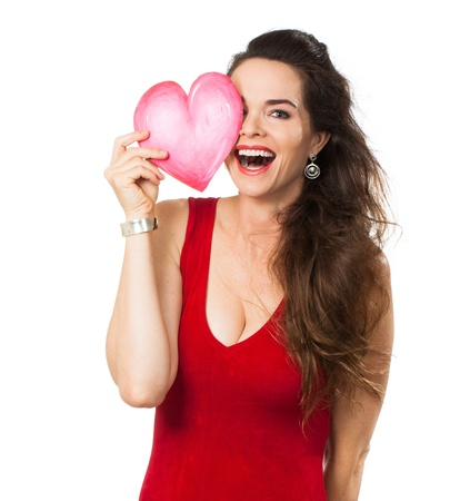 attractive gorgeous: A happy laughing woman holding a red love heart in front of one eye  Isolated on white  Stock Photo