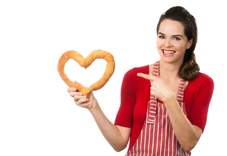A beautiful woman wearing an apron smiling and pointing  at a love heart made out of bread  Isolated on white  photo