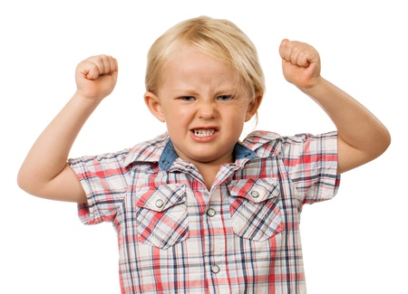A frustrated and angry young boy with fists raised in the air and pulling a face  Isolated on white  photo