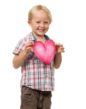 A very cute little boy smiling and holding a love heart for Valentine Stock Photo