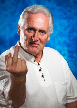 An angry grumpy mature man giving the rude middle finger and looking at camera
