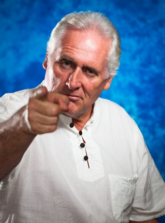 mean: A serious and angry looking man pointing and looking  at camera  Stock Photo
