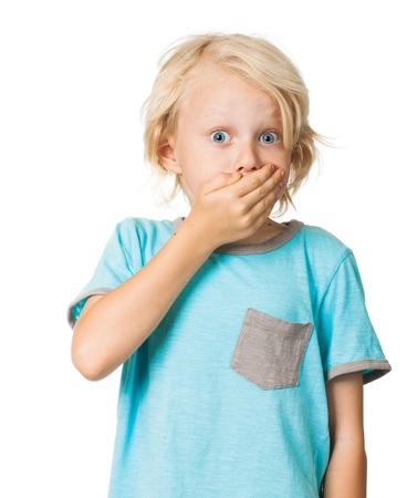 A shocked frightened young boy covering his mouth with his hand and staring wide eyed at the camera  Isolated on white