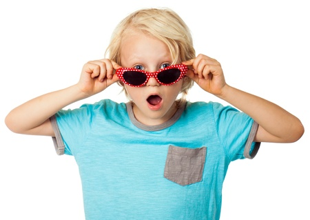 A cute surprised young boy looking over his sunglasses at the camera  Isolated on white