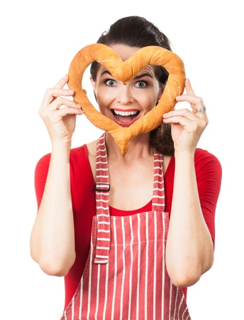 A beautiful happy woman wearing an apron is smiling and peeking through a love heart made out of bread  Isolated on white  photo