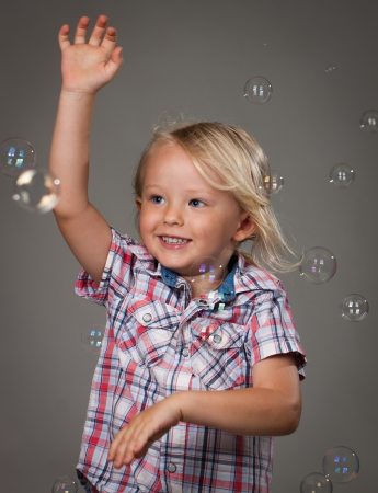 A very happy cute little boy catching soap bubbles Stock Photo - 18098713