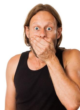 hombre preocupado: Un hombre sorprendido tapa la boca con la mano aislado en blanco