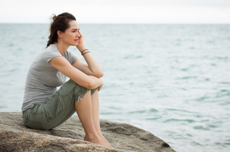 A sad and depressed woman sitting by the ocean deep in thought