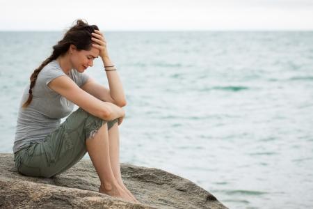 persona deprimida: Mujer trastornada y deprimida que se sienta por el oc�ano llorando, con la cabeza en la mano