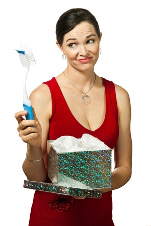 A disappointed woman looks at dish brush gift  Isolated on white  Stock Photo