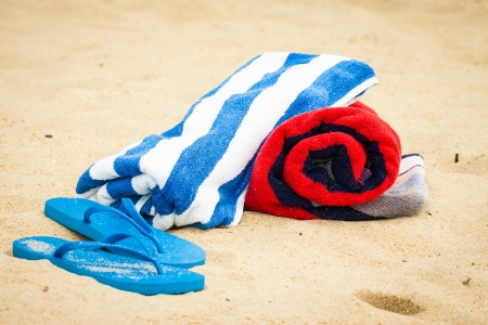 Rolled up beach towels and sandals or flipflops on a beach