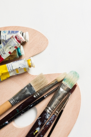Paint brushes and tubes of paint on a palette on top of a blank canvas photo