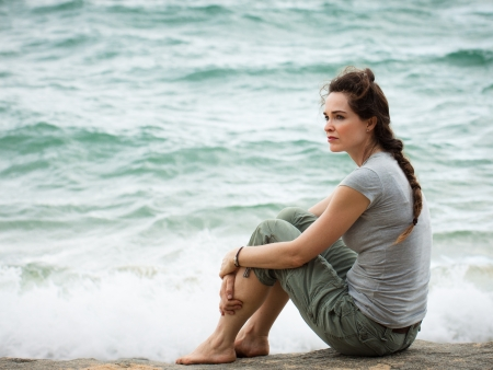 A sad and pensive woman sitting by the ocean deep in thought