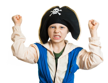A boy dressed up as a pirate pretending to be angry and dangerous. Isolated on white. photo