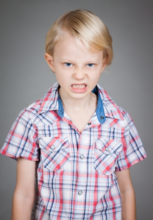 behaving: A frustrated and angry looking young boy  pulling a face. Isolated on white.