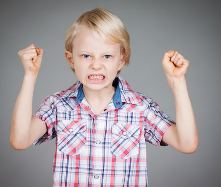 hyperactivity: A frustrated and angry looking young boy with fists clenched and pulling a face. Isolated on white.