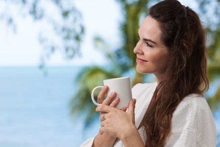 woman bathrobe: Close-up portrait of a beautiful woman enjoying her morning coffee or tea on a tropical balcony. Stock Photo