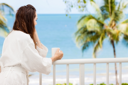 Woman in bath robe looking at beautiful ocean view  from a tropical balcony with morning coffee. Stok Fotoğraf
