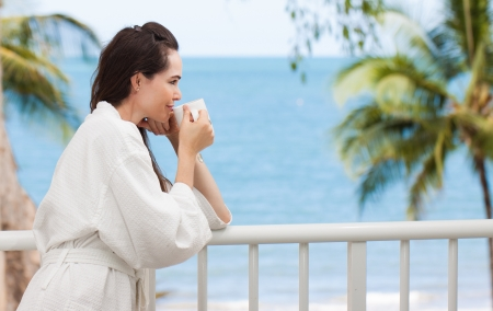 balcony view: Beautiful woman drinking her morning coffee or tea on a tropical balcony.