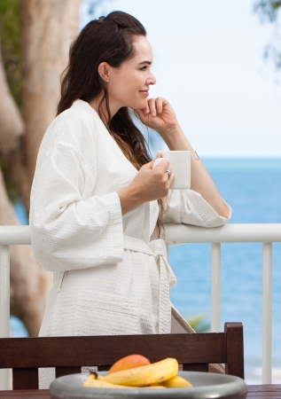 Woman relaxing with her breakfast coffee or tea on a tropical balcony. photo