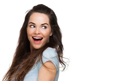 Een gelukkige verraste vrouw die over haar schouder op kopie-ruimte. Geïsoleerd op wit.