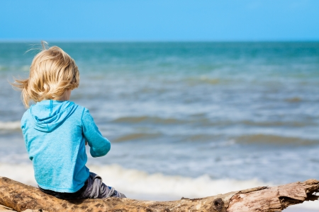 A young carefree child sitting on a log at the beach. photo