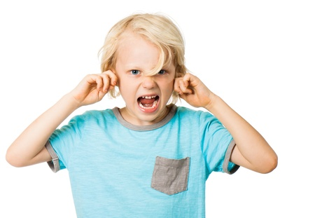 A young angry boy screaming and blocking his ears. Isolated on white. photo