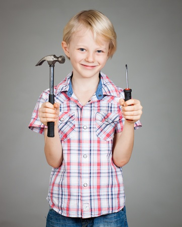 A cute smiling boy holding a hammer and a screwdriver