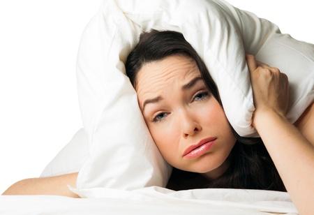 Una donna stanca insonne con il cuscino sopra la testa. Isolato su bianco. Archivio Fotografico - 22813022