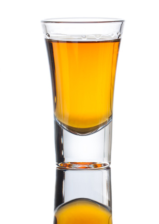shot: A small shot glass of delicious single malt whiskey with reflection . Isolated on white Stock Photo