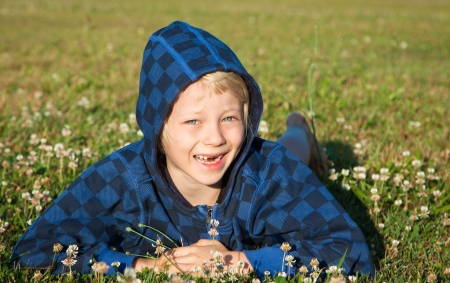 A cute happy smiling boy lying in grass with clover with missing front teeth.
