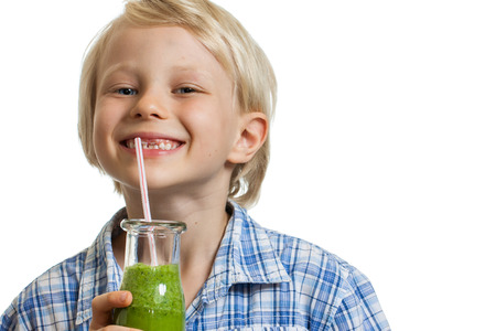 A smiling cute young boy drinking a green smoothie from a straw  Isolated on white