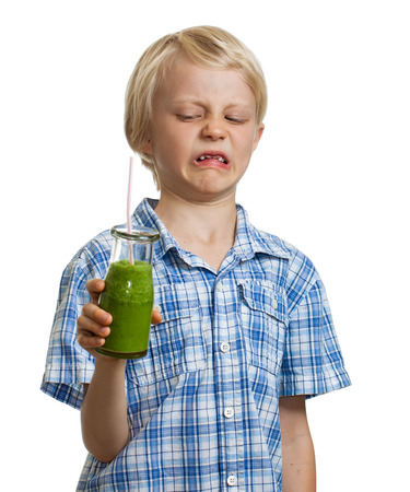 is disgusted: A funny boy holding a green smoothie looking disgusted  Isolated on white