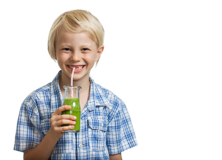 A cute young healthy boy drinking a green smoothie or juice through a straw  Isolated on white  photo