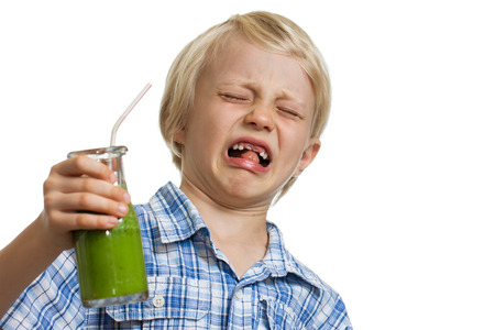 A young boy looking very disgusted holding a green smoothie  Isolated on white