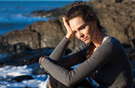 Sad woman sitting by the ocean deep in thought photo