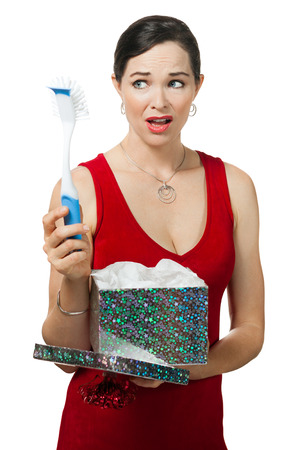 A disappointed woman looks at dish brush gift  Isolated on white  photo