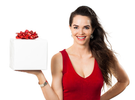 beautifully wrapped: A happy woman in a red dress smiling and holding out a beautifully wrapped christmas gift  Isolated on white