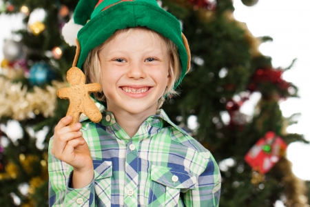 A cute boy dressed as Santas helper or an elf is holding gingerbread man and smiling in front of a Christmas tree. Isolated on white. photo