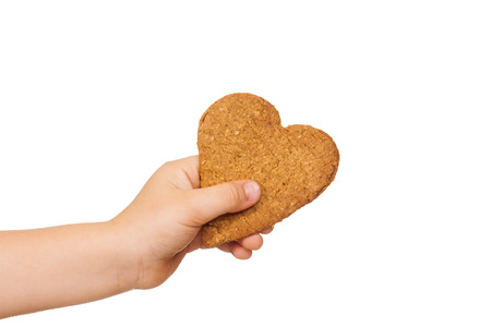 A childs hand is holding a love shaped gingerbread cookie. Isolated on white. photo