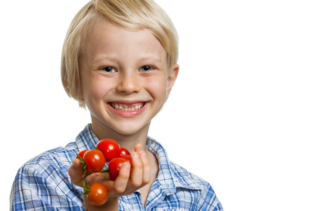 ripened: A cute happy blond boy holding a bunch of vine ripened organic cherry tomatoes. Isolated on white.