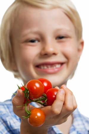 Close-up of a cute boy holding out a bunch of vine ripened organic cherry tomatoes. Isolated on white. photo