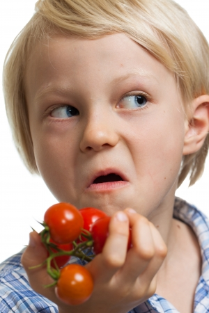 ripened: A funny boy holding a bunch of vine ripened organic cherry tomatoes and pulling a face. Isolated on white.