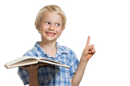 boy book: A cute smiling young boy holding a book and pointing to copy-space. Isolated on white.