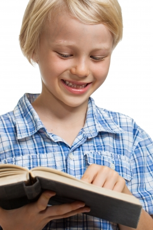 Close-up of a  cute young boy holding and reading a thick book. Isolated on white. photo