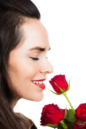 Close-up portrait of a beautiful woman smiling and smelling a rose. Isolated on white. Stock Photo