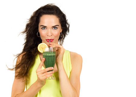 drink: Beautiful healthy woman drinking an organic green smoothie. Isolated on white.