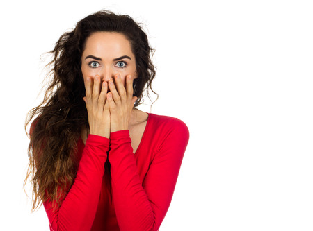 A scared and shocked woman covering her mouth in surprise. Isolated on white. Stock Photo