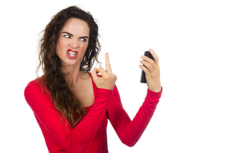 annoyed: A very angry, annoyed and frustrated woman  giving the finger to the phone in rage. Isolated on white. Stock Photo