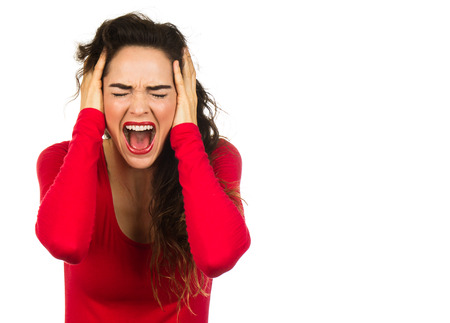 A very angry and frustrated woman screaming and covering her ears. Isolated on white.